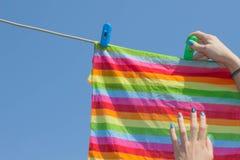 Una mujer colgó el lavadero lavado al aire libre Lavadero de sequía de la muchacha en una línea de ropa en el sol en el al aire l Imagen de archivo