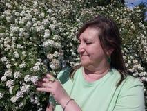 Una mujer comprueba el crecimiento de arbustos decorativos Foto de archivo
