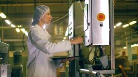 Una mujer comprueba el equipo de la fábrica, trabajando en una planta de la producción alimentaria almacen de video