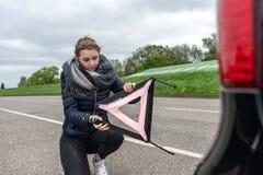 Una mujer con una avería del coche montó el triángulo amonestador foto de archivo libre de regalías