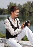 Una mujer con el ordenador portátil en cvb del parque Fotografía de archivo libre de regalías