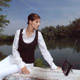Una mujer con el ordenador portátil en parque Foto de archivo