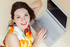 Una mujer con el ordenador portátil está en el sofá Imágenes de archivo libres de regalías