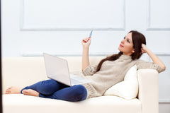 Una mujer con el ordenador portátil está en el sofá fotografía de archivo