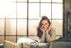 Una mujer con el pelo marrón largo que se sienta en un sofá Fotos de archivo