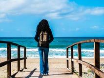 Una mujer con el pelo negro tomado de detrás con una mochila turística, caminando hacia la playa en una trayectoria de madera, lo fotos de archivo libres de regalías