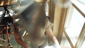 Una mujer con el pelo rizado se sienta cerca de una ventana en un café y hojea a través de un periódico Visión desde arriba
