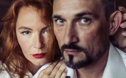 Una mujer con el pelo rojo y los labios rojos que miran directamente en la cámara Fotos de archivo