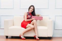 Una mujer con el regalo se está sentando en el sofá Fotografía de archivo