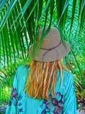 Una mujer con el sombrero de paja en parte trasera con las palmas Imagen de archivo libre de regalías