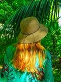 Una mujer con el sombrero de paja en parte trasera con las palmas Imagenes de archivo