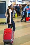 Una mujer con equipaje en el aeropuerto Imagen de archivo libre de regalías