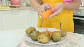 Una mujer con la manicura anaranjada que pela una zanahoria almacen de video