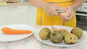 Una mujer con la peladura anaranjada de la manicura patatas almacen de metraje de vídeo
