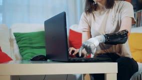 Una mujer con los trabajos de mano artificiales con un ordenador portátil, cierre para arriba almacen de metraje de vídeo