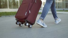 Una mujer con una maleta que dirige al edificio del aeropuerto Primer de las piernas almacen de video