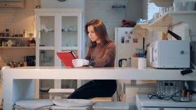 Una mujer con una mano prostética está trabajando con una tableta en una cocina