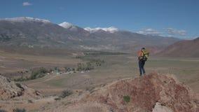 Una mujer con una mochila y viajes de la cámara en las montañas almacen de video