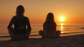 Una mujer con su hija que se sienta de lado a lado en la arena en una actitud del loto, mirando la puesta del sol sobre el mar fotografía de archivo