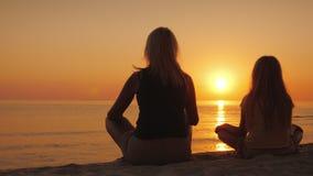 Una mujer con su hija que se sienta de lado a lado en la arena en una actitud del loto, mirando la puesta del sol sobre el mar foto de archivo libre de regalías