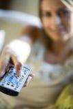 Una mujer con su telecontrol de la TV Imagen de archivo