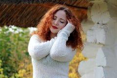 Una mujer con sus ojos cerró soportes cerca de la casa vieja en un suéter hecho punto blanco y lleva a cabo sus manos en su cabez fotografía de archivo libre de regalías