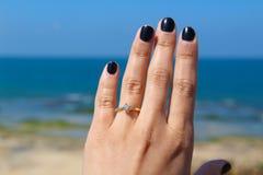 Una mujer con un anillo que sostiene un vidrio de vino con vistas al mar Fotos de archivo