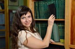 Una mujer con un artilugio en la biblioteca Fotos de archivo libres de regalías