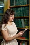 Una mujer con un artilugio en la biblioteca Fotografía de archivo