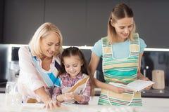 Una mujer con un libro de la receta ayuda a una muchacha y a su abuela a preparar una torta Fotografía de archivo libre de regalías