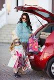 Una mujer con un niño después de la carga que hace compras el coche Foto de archivo