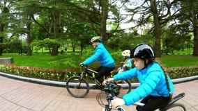 Una mujer con un niño monta una bicicleta al lado de una muchacha en una bicicleta Cámara lenta almacen de video