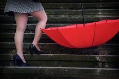 Una mujer con un paraguas rojo foto de archivo libre de regalías