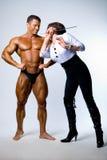 Una mujer con un puntero al lado de un bodybuilder Imágenes de archivo libres de regalías