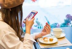 Una mujer con un smartphone está tomando a imagen del macarrones y una taza de té en un café fotografía de archivo