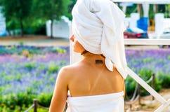 Una mujer con un tatoo en una toalla de baño se está sentando en un salón Fotografía de archivo