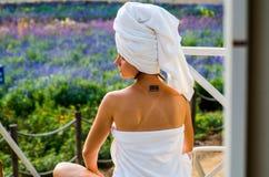 Una mujer con un tatoo en una toalla de baño se está sentando en un salón Fotografía de archivo libre de regalías
