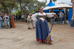 Una mujer con un traje medieval que sostiene una escoba Imágenes de archivo libres de regalías