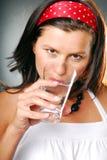 Una mujer con un vidrio de agua imagen de archivo libre de regalías