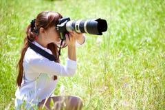 Una mujer con una cámara en el campo Fotografía de archivo libre de regalías