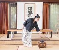 Una mujer con una ceremonia de té de tetera-China Fotos de archivo libres de regalías