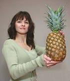 Una mujer con una manzana del pino Imágenes de archivo libres de regalías