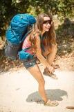 Una mujer con una mochila abotona las sandalias Imagen de archivo