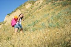 Una mujer con una mochila mira para arriba la colina y la mirada detrás Fotografía de archivo libre de regalías
