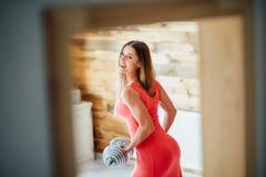 Una mujer con una pesa de gimnasia en un vestido rosado sonríe Foto de archivo