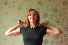 Una mujer con una pesa de gimnasia ha estado cargando Foto de archivo libre de regalías