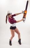 Una mujer con una sierra eléctrica en su mano imagen de archivo libre de regalías