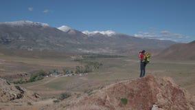 Una mujer con viajes de una mochila en las monta?as almacen de metraje de vídeo