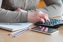 Una mujer conduce cálculos de la contabilidad en la oficina fotos de archivo