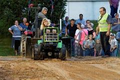 Una mujer conduce en un tirón del tractor del césped imagenes de archivo
